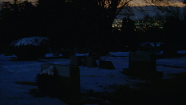 PAN LEFT TO RIGHT THEN BACK SHOWS SNOW COVERED HILLSIDE CEMETERY WITH MOUNTAIN RANGE IN BACKGROUND. GRAVEYARD HAS TOMBSTONES, HEADSTONES, GRAVESTONES.
