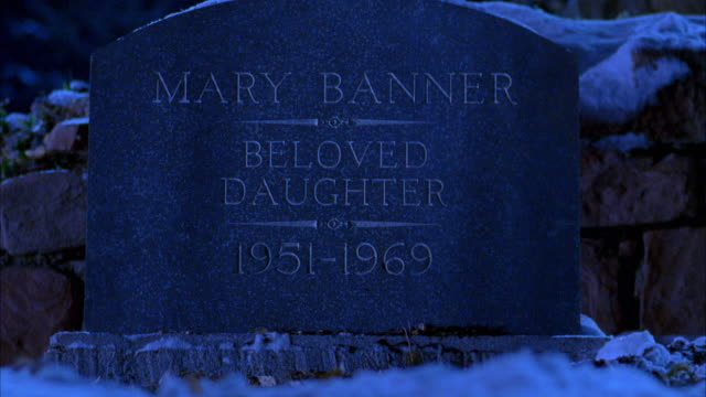 CLOSE ANGLE OF TOMBSTONE READING 'MARY BANNER BELOVED DAUGHTER 1951-1969.' GRAVE IS COVERED IN SNOW. HEADSTONES.