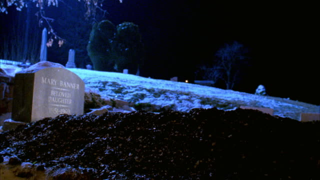 """WIDE ANGLE OF FRESHLY DUG GRAVE WITH TOMBSTONE READING """"MARY BANNER BELOVED DAUGHTER."""" LIGHT FROM FLASHLIGHT OR HEADLIGHTS SHINES ON GRAVESTONE MOMENTARILY. SNOWY CEMETERY IN BACKGROUND."""