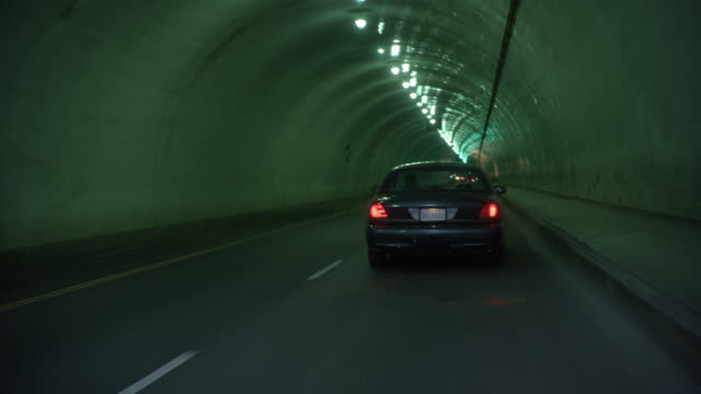 WIDE ANGLE MOVING POV FORWARD OF SEDAN CAR WITH CALIFORNIA LICENSE PLATE DRIVING THROUGH LIGHTED TUNNEL PAST SLEEPING HOMELESS. CAMERA PASSES CAR FOCUSES ON TUNNEL. COULD BE POV OF CAR FOLLOWING AND PASSING SEDAN.