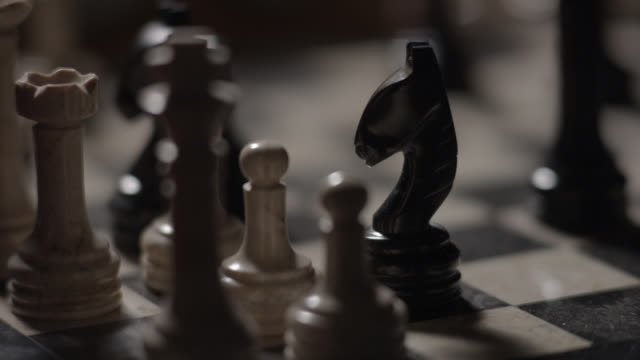close angle of chess match. hands of men move chess pieces. games. board games. - chess stock videos & royalty-free footage