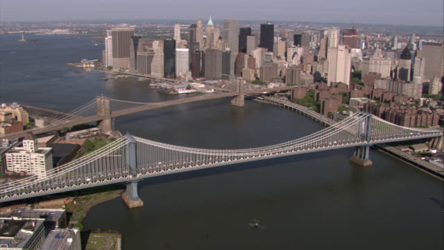AERIAL OF MANHATTAN AND BROOKLYN BRIDGES. EAST RIVER. SKYSCRAPERS AND HIGH RISE OFFICE OR APARTMENT BUILDINGS. CITY SKYLINE. NEW YORK HARBOR IN BG.