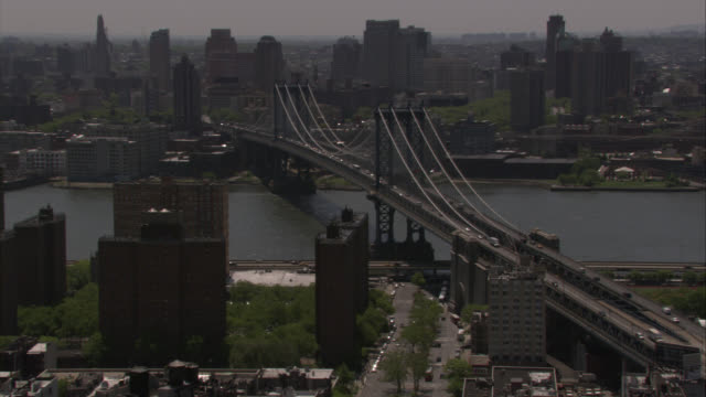 vídeos de stock e filmes b-roll de aerial of manhattan bridge, brooklyn and manhattan. east river. cars driving on freeway or highway. cars on lower level of bridge stopped in traffic. nypd, police cars and officers. high rises. multi-story office or apartment buildings. cities. urban area - ponte de manhattan