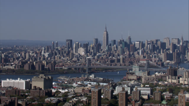 aerial of new york city, manhattan and brooklyn. williamsburg bridge over east river. skyscrapers and high rise office or apartment buildings. new york city skyline and urban area. multi-story buildings. empire state building. - williamsburg bridge stock videos & royalty-free footage