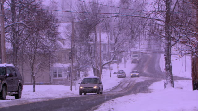 pan down from high angle of bare trees branches covered in snow to wide angle of cars driving down snow covered street. church and spire in bg. cars have headlights on. could be small town. winter. could be residential area. - spire stock videos & royalty-free footage