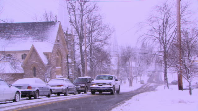 wide angle of snow covered street in residential area. trees with bare branches and church line street. overcast. could be small town or rural area. cars with headlights drive down street. - town stock videos & royalty-free footage
