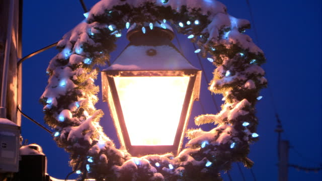 close angle of street lamp decorated with christmas wreath. christmas lights on wreath. snow. telephone wires visible in bg. - リース点の映像素材/bロール