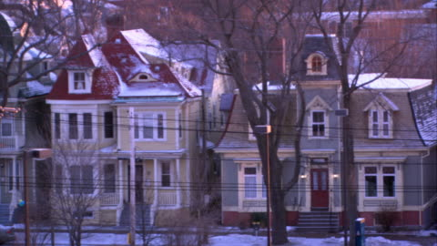 vídeos y material grabado en eventos de stock de pan left to right of townhouse or houses in residential area. urban area. snow covers roofs and ground. telephone wires and poles in fg. cemetery in bg. bare branches on trees. nova scotia flag. - estilo victoriano