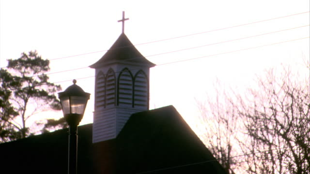 UP ANGLE OF STEEPLE AND CROSS ON TOP OF CHURCH. BARE TREE BRANCHES IN BG. TELEPHONE WIRES AND LAMP POST IN FG.