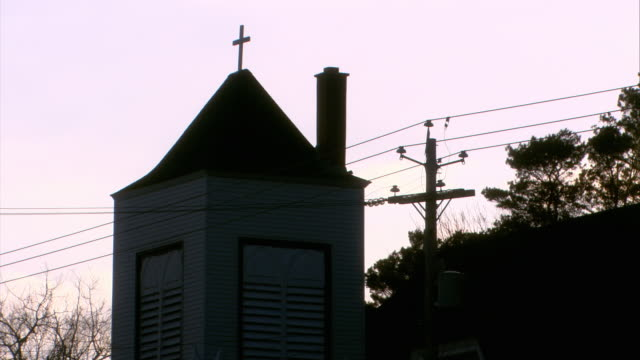 medium angle of steeple and cross on top of church. bare tree branches in bg. telephone wires and chimney visible. - steeple stock videos & royalty-free footage
