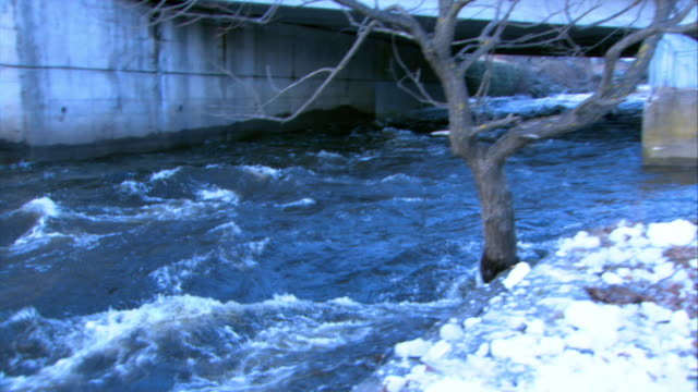 stockvideo's en b-roll-footage met pan right to left from overpass or bridge with creek, stream, or river flowing underneath to medium angle of sewage or drainage pipe. could be bridge. pipe in barricade, embankment, or dam. tree with bare branches in fg. rapids. - bare tree
