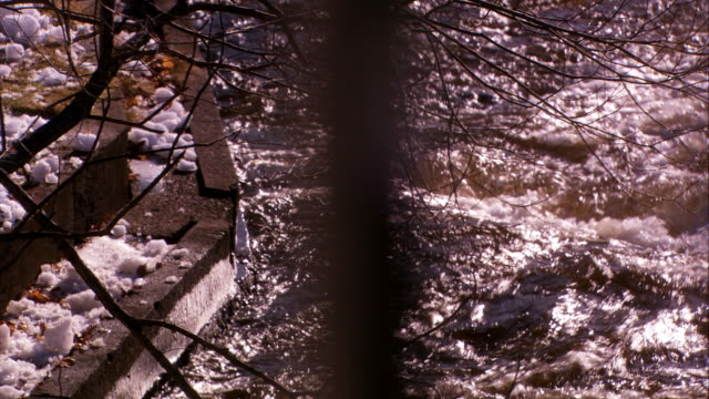 stockvideo's en b-roll-footage met medium angle of water in creek, stream, or river through pov of bars or rails. could be fence or bridge. rapids. bare tree branches and snow on ground. winter. power line or cable in fg. - bare tree