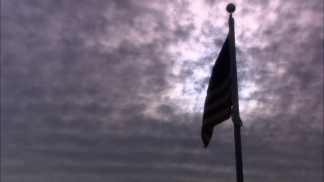 up angle of american flag flying on flagpole against blue sky with clouds. - fahnenstange stock-videos und b-roll-filmmaterial