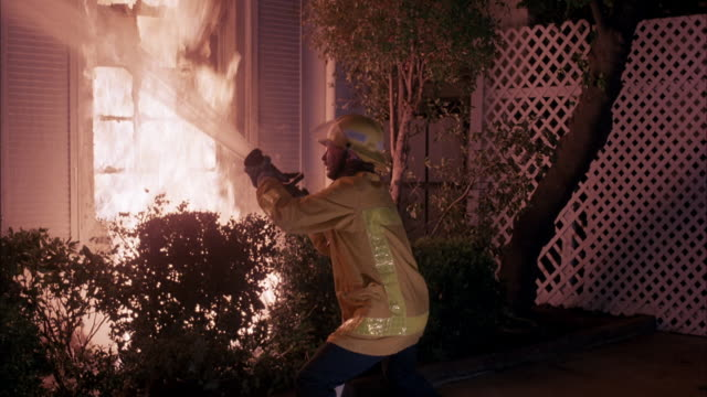 medium angle of burning house. shot begins with fireman standing in front of burning house. fireman then turns around and begins to spray house with fire hose. man burning then walks out from behind house to right of clip. man is completely on fire. walks - fire hose stock-videos und b-roll-filmmaterial