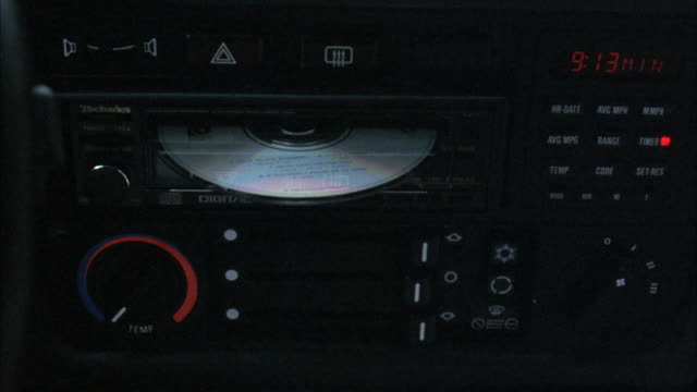 close angle of car compact disc player. female passenger takes cd out male driver puts it back in. passenger changes compact disc a total of 6 times. insert. - compact disc player stock videos & royalty-free footage
