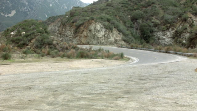 wide angle of mountain highway. red volkswagen beetle or bug drives left to right away from camera. red ford mustang comes from opposite direction and approaches camera moving right to left. blue mustang drives left to right away from camera. cars.preview - ford mustang stock videos and b-roll footage