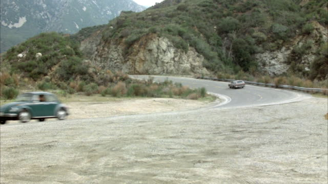WIDE ANGLE OF MOUNTAIN HIGHWAY.  BLUE MUSTANG DRIVES LEFT TO RIGHT AWAY FROM CAMERA. BROWN STATION WAGON COMES FROM OPPOSITE DIRECTION AND APPROACHES CAMERA MOVING RIGHT TO LEFT. BLUE MUSTANG COMES FROM SAME DIRECTION, APPROACHES CAMERA MOVING RIGHT TO LE