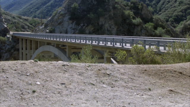 medium angle of a bridge spanning a canyon with mountains behind it. vw volkswagen beetle drives across from left to right. sedan drives across from right to left. another sedan crosses from left to right. several more cars continue to cross bridge from b - volkswagen stock-videos und b-roll-filmmaterial