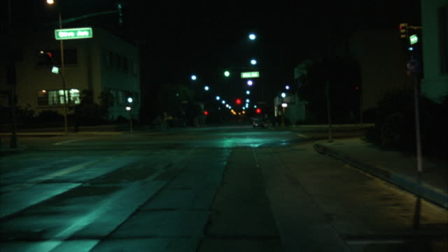 PROCESS PLATE SIDE POV DRIVING THROUGH INDUSTRIAL AND DOWNTOWN AREAS. TRAFFIC ON BOTH SIDES OF STREET. GO OVER FREEWAY OVERPASS, CITY LIGHTS VISIBLE IN BACKGROUND. ENTERS DOWNTOWN AREA, PASSES  SEVERAL SHOPS.PREVIEW FILE HAS BEEN TRIMMED FROM MASTER CLIP