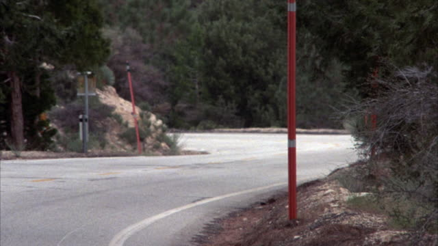 medium angle of yellow chevrolet camaro driving on a mountain road towards camera and off screen. - 1987 stock-videos und b-roll-filmmaterial