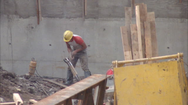 medium angle of construction worker on a construction site tying two shovels together. - baustelle stock-videos und b-roll-filmmaterial