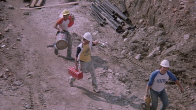 MEDIUM ANGLE OF THREE CONSTRUCTION WORKERS ON CONSTRUCTION SITE CARRYING EQUIPMENT WALKING TOWARD CAMERA, THEN MAKE LEFT TURN AS CAMERA PANS AND THEY WALK AWAY FROM CAMERA.