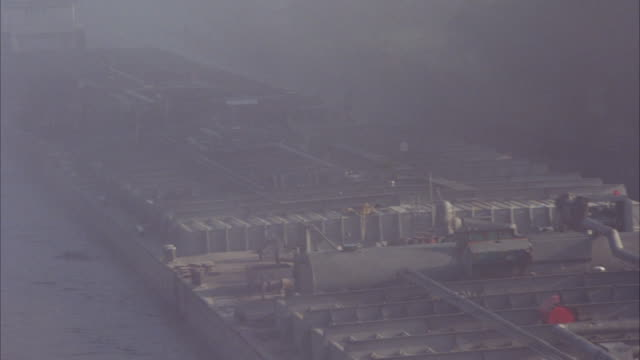 high angle down of barge in fog moving toward camera. camera pans right to show barge going under drawbridge. bridge attendant visible. - drawbridge stock videos and b-roll footage