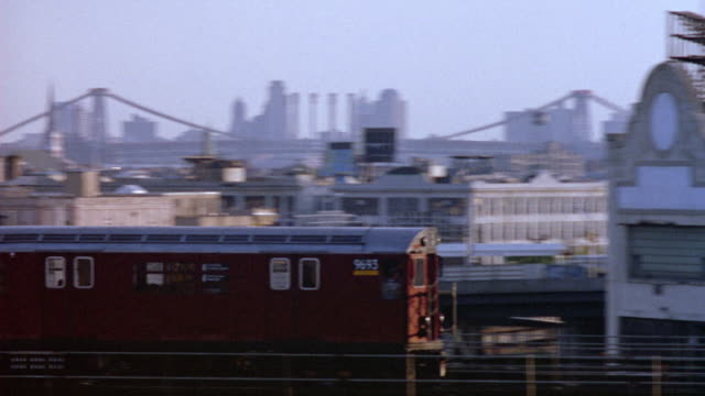 wide angle of outer new york city area. see george washington bridge in background. a-train runs from left to right in foreground. shot pans right to follow a-train, drives by warehouses and buildings. see brooklyn city skyline in background. sunset. - anno 1994 video stock e b–roll