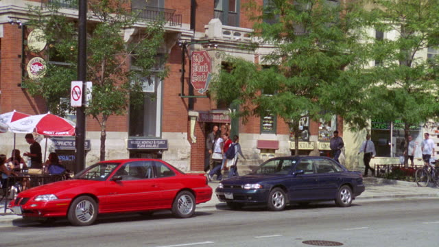 "zoom in on ""the black sock"" and sign. could be a bar, pub or restaurant. brick building. tree branches. cars driving on city street. pedestrians, people walking on sidewalk.<p><a href=""https://www.sonypicturesstockfootage.com/footage?kid=4337"">for day-nig - 1996 video stock e b–roll"