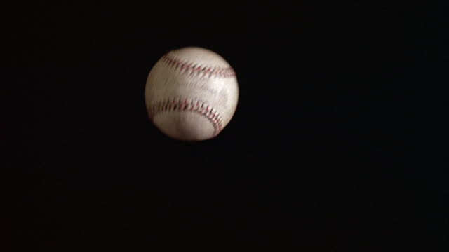 medium angle - night- black sky. see baseball slowly fly into shot from behind and out of shot. - baseball sport stock videos & royalty-free footage