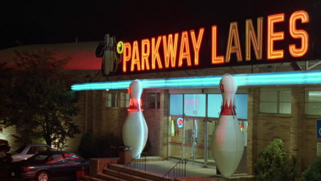 """medium angle of entrance to """"parkway lanes"""". see two large pins outside of entrance. people walk out of door at end. - ボーリング場点の映像素材/bロール"""