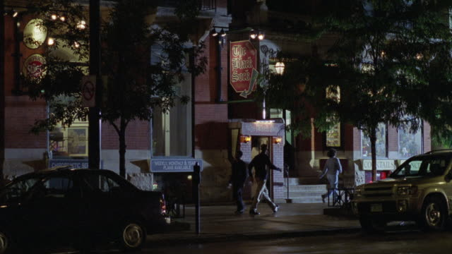 "pan down from multi-story brick apartment buildings to ""the black sock"". could be restaurant, bar or pub. cars on city street. pedestrians, people walking on sidewalk.<p><a href=""https://www.sonypicturesstockfootage.com/footage?kid=4337"">for day-night mat - stockwerk stock-videos und b-roll-filmmaterial"