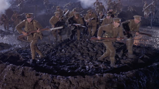 wide angle of world war i allied soldiers with rifles going into battle. see flashes of light coming from left. soldiers walk over muddy mound that explodes in front of them. see smoke filled crater and soldiers lying on mud. explosions. action. battlefie - prima guerra mondiale video stock e b–roll