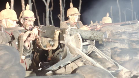 medium angle of world war i era german soldiers emerging from trench to fire machine guns. one soldier feeds ammunition into gun while the other aims. could be  maschinengewehr  08 (mg08) type machine gun. other soldiers aim and fire rifles. soldiers wear - world war one stock videos & royalty-free footage