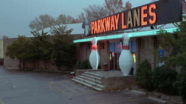 "vídeos de stock, filmes e b-roll de medium angle of ""parkway lanes"" bowling alley. shot pans left to parking lot that is empty other than one grey ford explorer suv. pans back to entrance to bowling alley. - cancha de jogo de boliche"