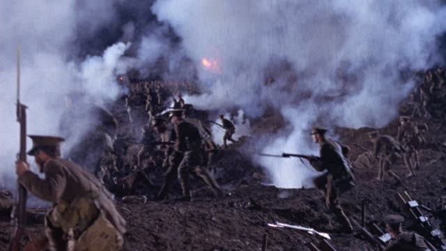wide angle of battlefield with allied soldiers hiding in trenches or foxholes. waves of soldiers emerge from foxholes and move right to left. see rockets explode in scattered areas of battlefield. soldiers fall dead or wounded. smoke covers battlefield. e - prima guerra mondiale video stock e b–roll
