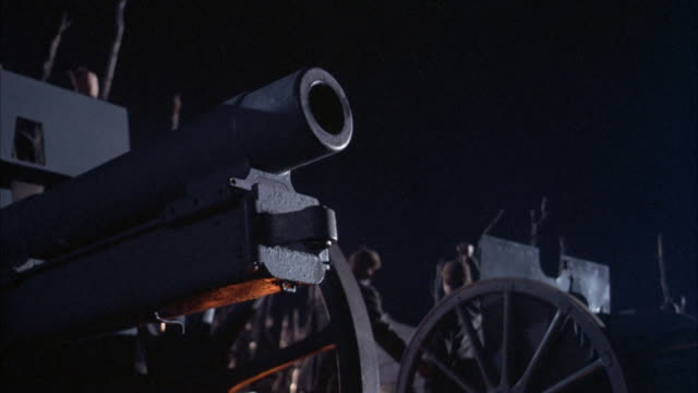 close angle of world war i era cannon on night battlefield. german soldiers walk in background. see cannon fire one shot generating sparks and cloud of smoke. explosions. - cannon stock videos & royalty-free footage