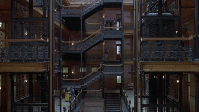MEDIUM ANGLE OF ATRIUM LOBBY OF BRADBURY BUILDING. PANS UP, SEE DIFFERENT LEVELS OF STAIRS. BUSINESSPEOPLE WALKING AROUND BUILDING. PANS UP TO GLASS ROOF.  COULD BE USED FOR OFFICE BUILDING OF PROFESSIONALS - LAWYERS, DOCTORS, ARCHITECTS, BUSINESSMEN. LOS