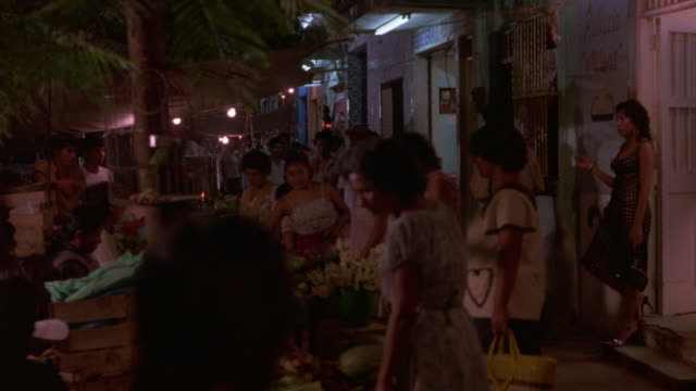 MEDIUM ANGLE OF PRODUCE STAND IN MARKETPLACE. SEVERAL PEOPLE BUYING AND SELLING VARIOUS GOODS.