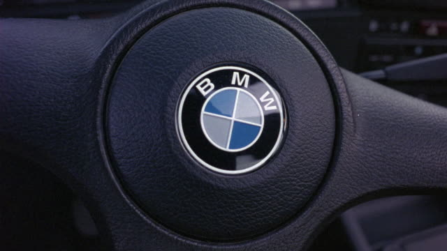 close angle of bmw steering wheel. blue and white bmw logo visible. wheel turns slightly to left. insert. - bmw stock videos & royalty-free footage
