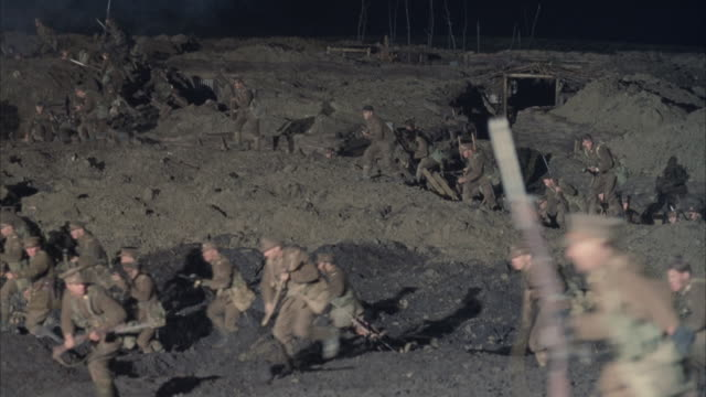 wide angle of battlefield with allied soldiers hiding in trenches or foxholes. waves of soldiers with rifles emerge from foxholes and move right to left. see rockets explode in scattered areas of battlefield. smoke covers battlefield. explosions. action. - prima guerra mondiale video stock e b–roll