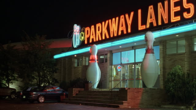 "medium angle of ""parkway lanes"" bowling alley entrance. see two large bowling pins in front of entrance. neon sign on top. - ボウリング点の映像素材/bロール"