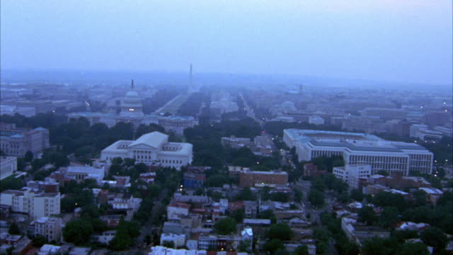 AERIAL OF WASHINGTON, D.C. CAMERA PANS FROM RIGHT TO LEFT ACROSS NATIONAL MALL. SEVERAL MONUMENTS VISIBLE. FOG ENVELOPS BACKGROUND.