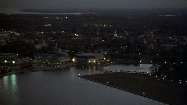 aerial moving past long island. see shoreline. buildings. dusk. street lamps are lit. shot pans down to black lincoln towncar driving on bridge from left to right. shot follows car as it drives out of shot. - long island video stock e b–roll