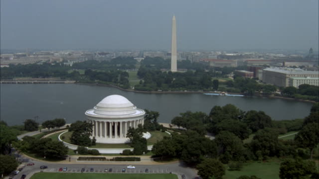 AERIAL OF NATIONAL MALL AND DOWNTOWN AREA. CAMERA FLIES OVER THOMAS JEFFERSON MEMORIAL AND CONTINUES TOWARD WASHINGTON MONUMENT, CURVES TO THE RIGHT AND ZOOMS IN ON DOWNTOWN AREA.