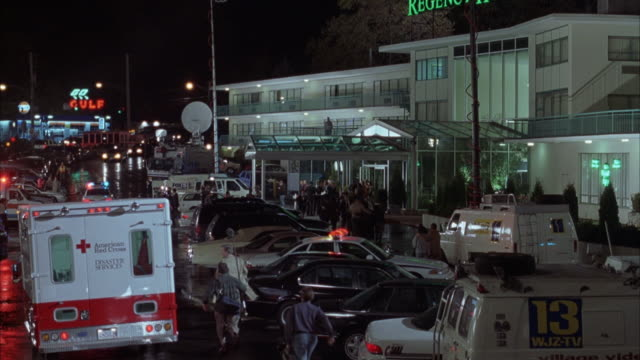 wide angle of royal regency hotel at night. see parking lot in foreground. shot pans up as ambulance drives away from camera with lights flashing. see crowd of people in front of hotel. news vans are parked in front. rained on streets. - queens new york city stock videos and b-roll footage