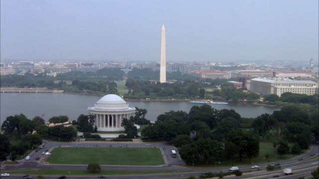 aerial of national mall and downtown area. camera flies over thomas jefferson memorial and continues toward washington monument, curves to the right and zooms in on downtown area. - washingtonmonumentet dc bildbanksvideor och videomaterial från bakom kulisserna