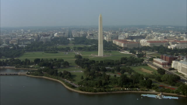 aerial of downtown area. camera flies over river toward washington monument, then zooms in on white house. - weißes haus stock-videos und b-roll-filmmaterial