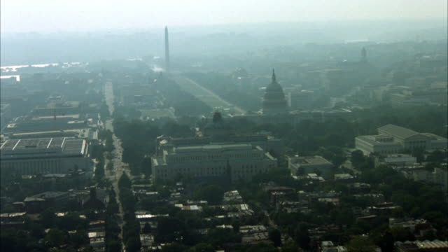 aerial of downtown area. camera flies toward capitol building. washington monument visible in background. smog envelops city. - 1987 stock-videos und b-roll-filmmaterial