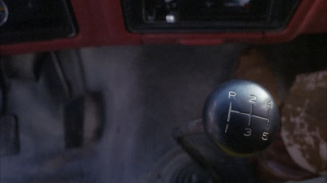 CLOSE ANGLE OF  BLACK SHIFTER OR MANUAL STICK SHIFT KNOB.  SHIFTER KNOB HAS REVERSE GEAR IN UPPER LEFT. SEE BROWN BOOT OR SHOE AND PANTS LEG  OF PASSENGER TO THE RIGHT OF SHOT. SEE BROWN DASHBOARD AND BLACK AIR CONDITIONING VENTS.